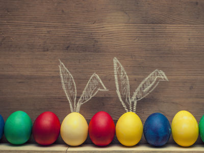 Easter eggs with cute rabbit ears on a wooden background textures, holiday decoration, Happy Easter!